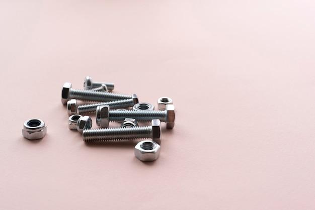 Плоские серебряные гайки и болты из нержавеющей стали лежат на столе, минималистичная концепция