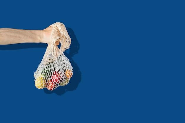色の壁にメッシュの綿のエコバッグを持っている手のシンプルな抽象的なイメージ、ゼロ廃棄物のリサイクル