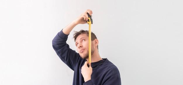 롤 테이프가있는 간단한 성인 십대 남성 사람이 벽에 높이를 측정