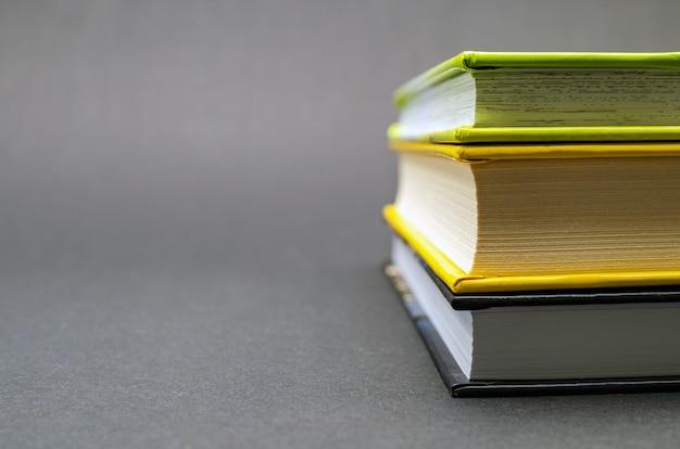 검정색 배경에 많은 양장본 책의 간단한 구성. 학교로 돌아가다. 교육 개념입니다. 공간을 복사합니다.