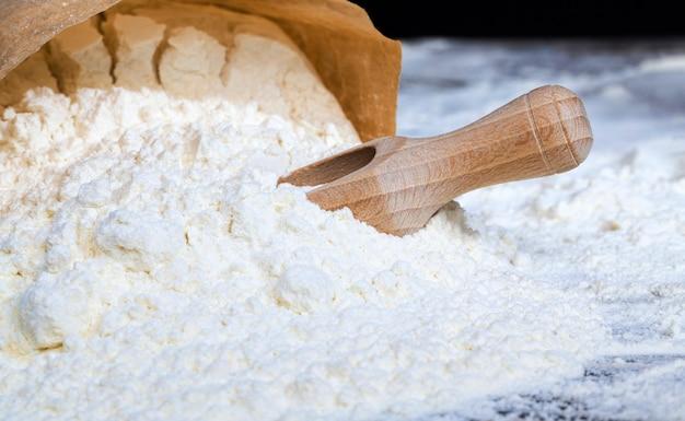 田舎の台所のテーブルで、調理中に小麦粉とシンプルな木のスプーン