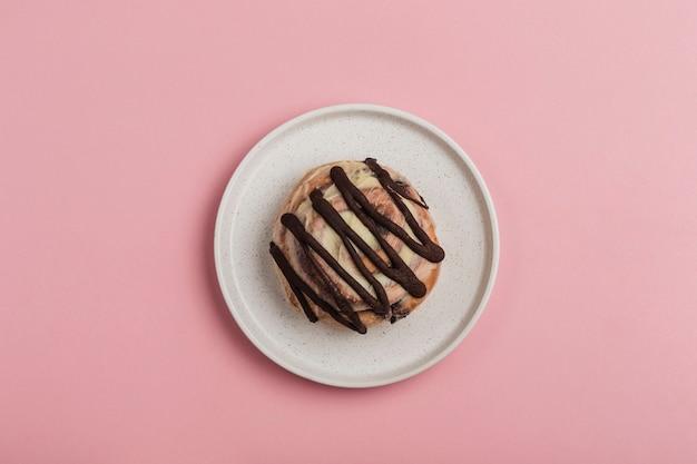 Булочка синабон с шоколадом лежит в тарелке на розовом фоне. американская классическая булочка.