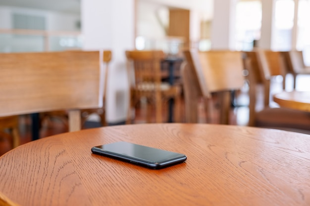 나무 탁자에 있는 검은색 휴대폰