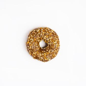 ナッツが分離された白い表面を持つ単一のチョコレート艶をかけられたドーナツ、上面図