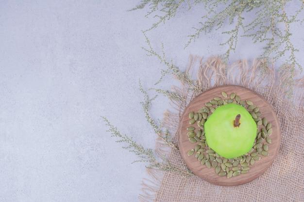 Единственная зеленая груша на деревянной доске с тыквенными семечками вокруг