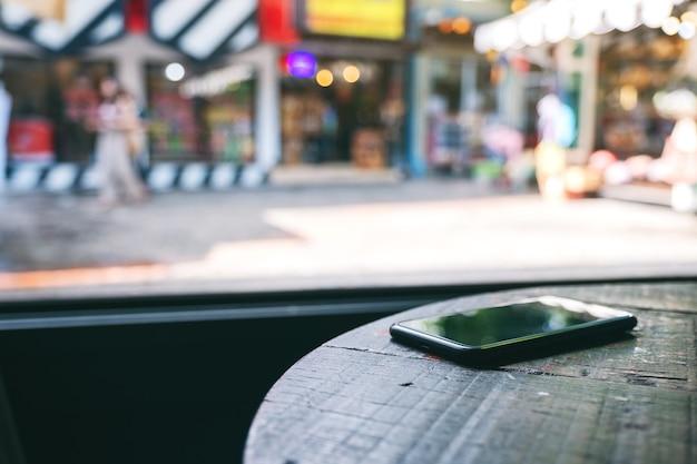 가게의 나무 탁자에 있는 한 대의 휴대폰