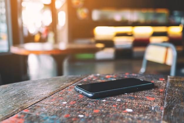 나무 탁자에 있는 한 대의 휴대폰