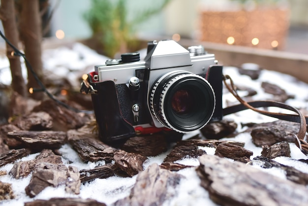 雪の降る地面にとどまる、1台の古いレトロな写真カメラ。