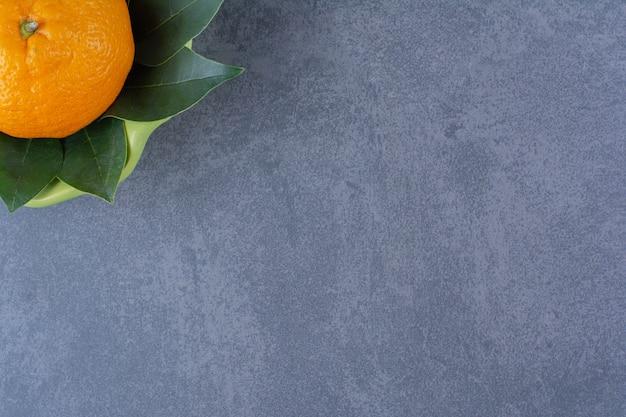 볼론 대리석 테이블에 나뭇잎이 있는 단일 오렌지.