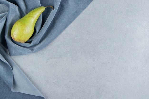 Единственная груша на куске ткани на мраморе