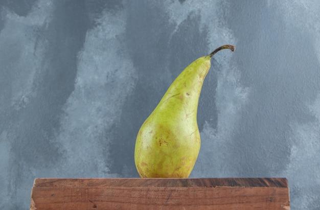 Одиночная груша на деревянной доске по мрамору