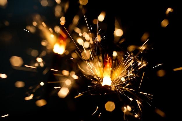金のフレアと火花のシャワーを放つ単一の線香花火