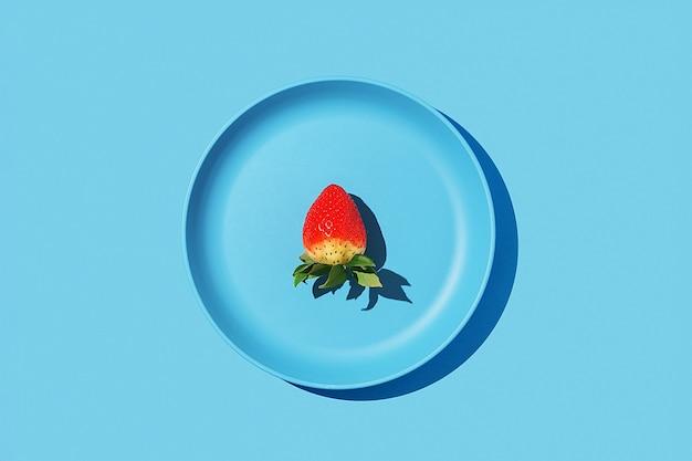 Одна клубника на синей тарелке на синем фоне. вид сверху.