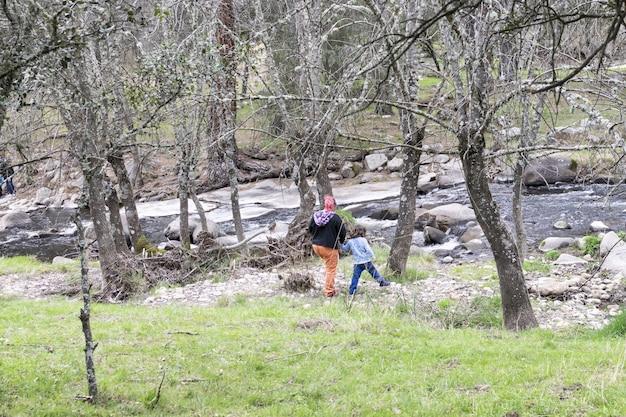 Семья с одним родителем гуляет по природе, избегая скопления людей.