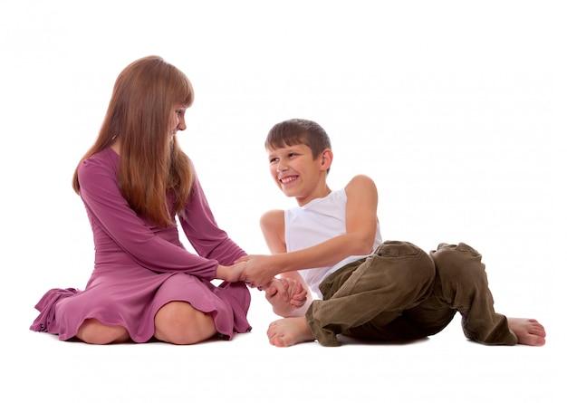 姉と弟は床に横に座って一緒にゲームをします。