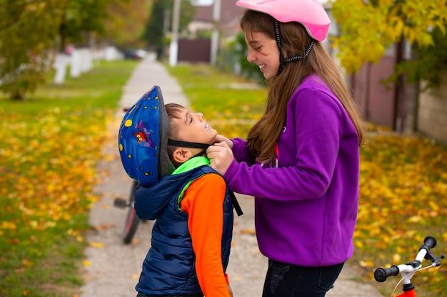Сестра помогает младшему брату надеть и закрепить защитный шлем на велосипед. дети улыбаются и веселятся. концепция отдыха и проведения времени.