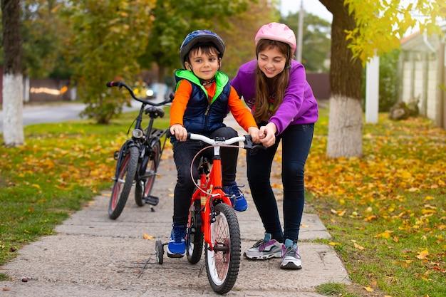 Сестра учит своего младшего брата кататься на велосипеде в осеннем парке в солнечную погоду. семья и здоровый образ жизни.