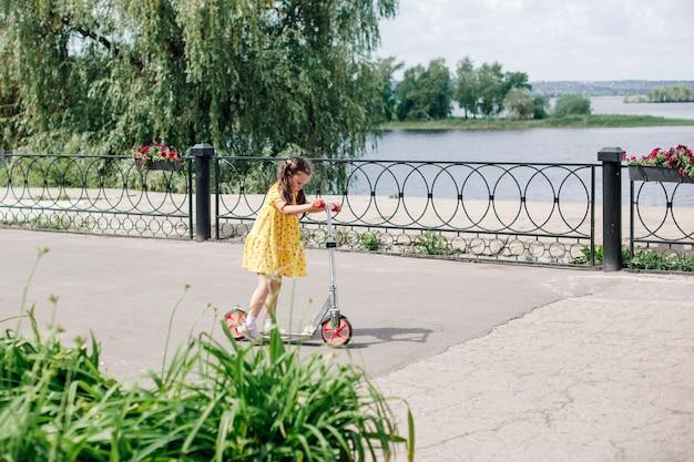 Шестилетняя девочка в желтом платье учится кататься на самокате, девочка на скутере по асфальту ...