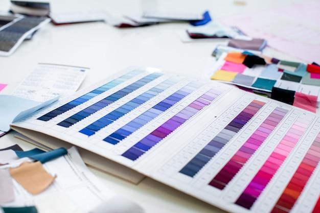 Эскиз платья и комплект ткани. эскизы одежды и образцы тканей на столе. дизайнер работает