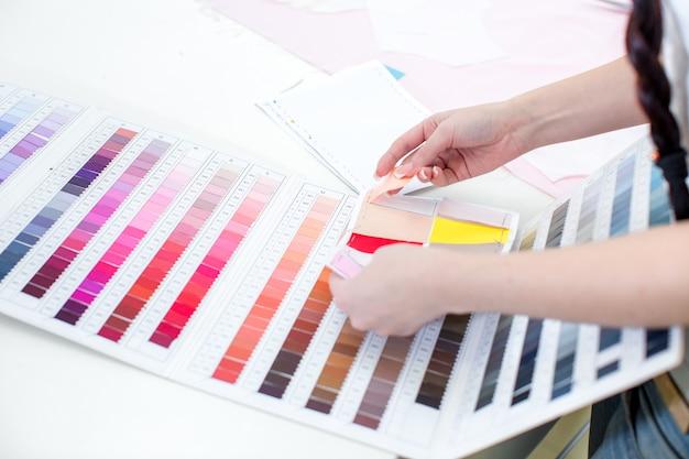 ドレスと布のセットのスケッチ。テーブルの上の服と生地のサンプルのスケッチ。デザイナーが働いています