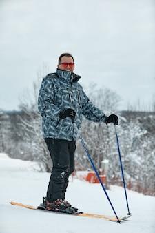 회색 재킷을 입은 스키어가 서리가 내린 날 슬로프를 내리막을 타고 있습니다.