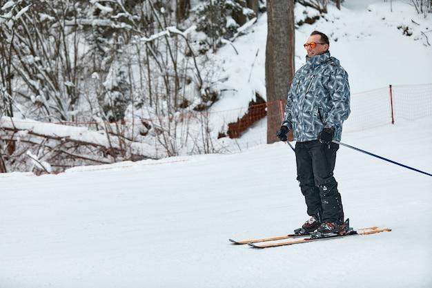회색 재킷을 입은 스키어가 서리가 내린 날 슬로프를 내리막을 타고 있습니다. 프리미엄 사진