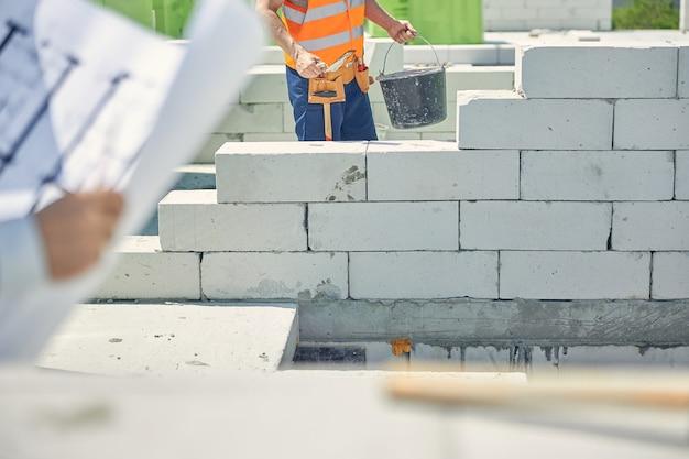 Опытный кавказский строитель мужчина держит в руке металлическое ведро