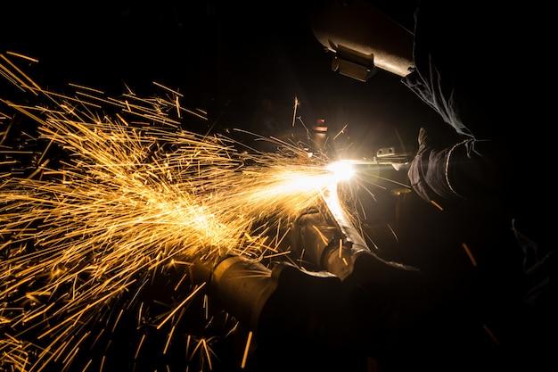 自動車部品を製造する熟練した溶接工。