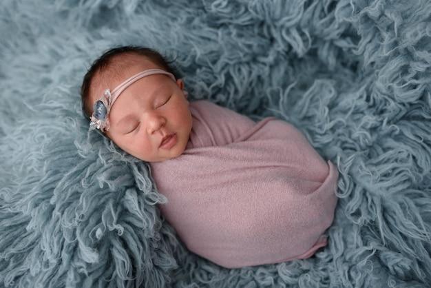 Спящий новорожденный ребенок в синем меху