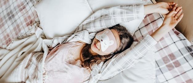 졸린 갈색 머리 소녀는 아침에 눈을 가리고 침대에 누워