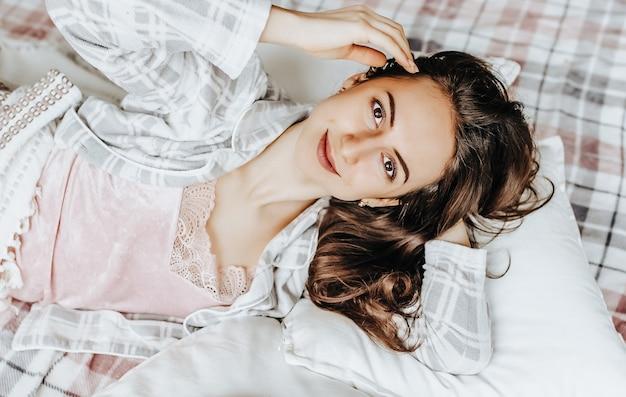 Сонная брюнетка лежит в постели с завязанными глазами и просыпается утром
