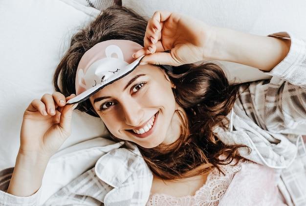 Сонная брюнетка лежит в постели с завязанными глазами