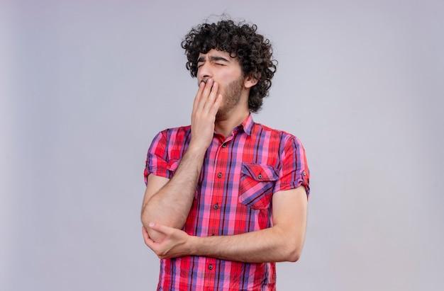 Сонный молодой симпатичный мужчина с вьющимися волосами в клетчатой рубашке, держащий руку во рту, зевает