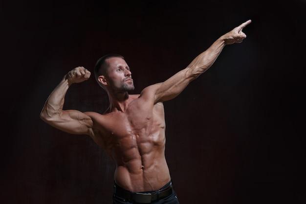 Стройный спортивный мужчина с голым торсом демонстрирует мускулы