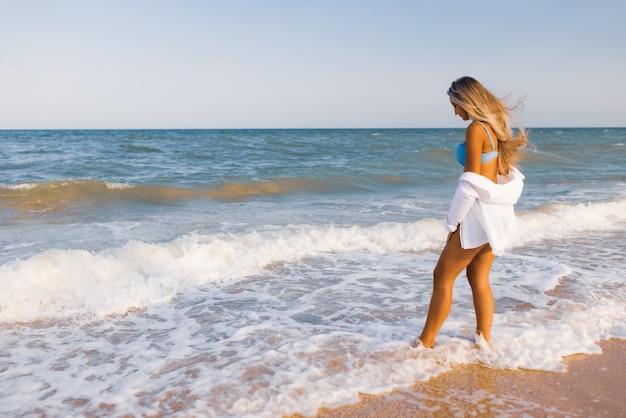 Стройная девушка в нежном голубом купальнике и рубашке гуляет по песчаному пляжу у синего моря