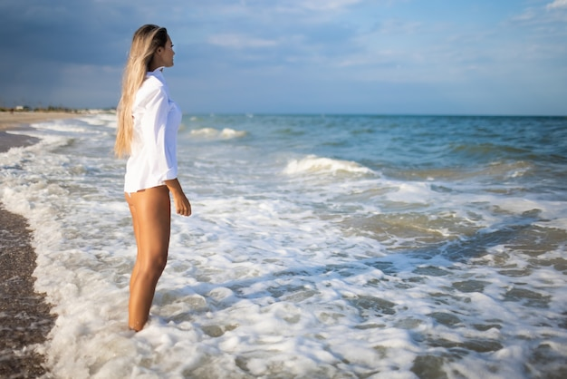 優しい青い水着とシャツを着たほっそりした女の子が青い海の近くの砂浜を歩きます