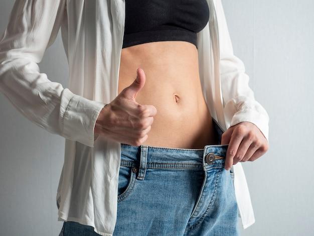 裸の胃を持つほっそりした女の子は、彼女がどのように体重を減らしたかを示しています。ジーンズは大きいです。親指を立てる、ダイエットの概念、減量、美しさ