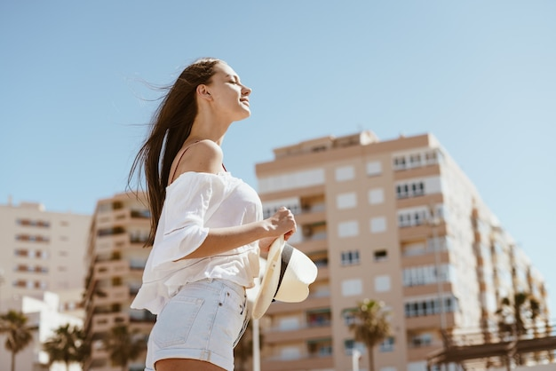 Стройная девушка с великолепной осанкой и гордо поднятой головой гуляет по пляжу.
