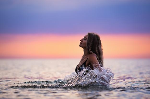 검은 수영복에 금발의 무성한 머리를 가진 날씬한 그을린 어린 소녀가 밝고 따뜻한 일몰을 배경으로 얕은 강어귀에 앉아있는 동안 옆으로 튀었습니다.