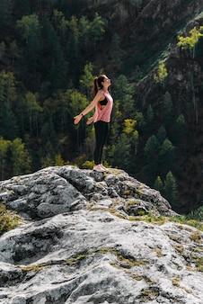 Стройная женщина занимается йогой на невероятном фоне природы. женщина занимается йогой на свежем воздухе. концепция здорового и йоги. девушка занимается гимнастикой на свежем воздухе в походе на природу.