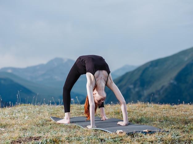 날씬한 여성이 레깅스와 티셔츠를 입고 산에서 자연 속에서 요가에 종사하고 있습니다.