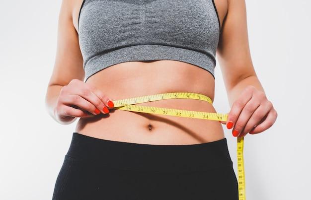 ほっそりした女性が巻尺で腰を測ります。白い背景に対して。