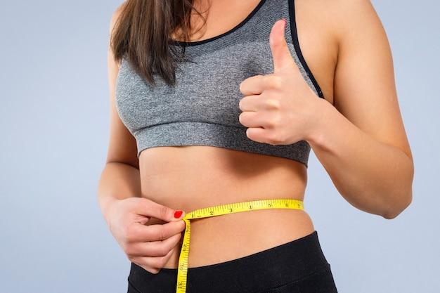 ほっそりした女性が巻尺で腰を測ります。黄色の背景のクローズアップに対して。