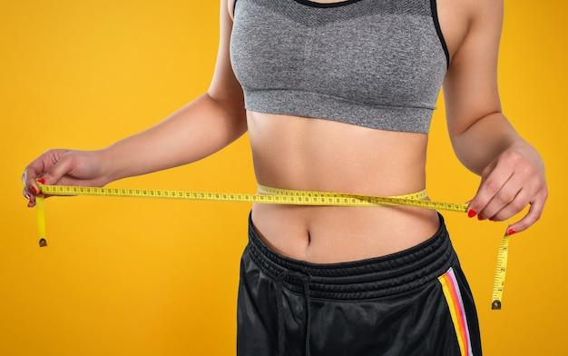 ほっそりした女性が巻尺で腰を測ります。黄色の背景に対して。