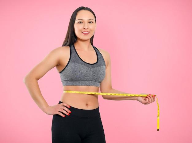 ピンクの背景に細身の女性が巻尺で腰を測っている。