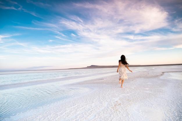 Стройная женщина бежит по берегу моря в платье.