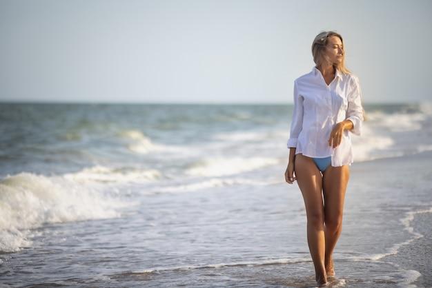優しい青い水着と白いシャツを着たほっそりした少女は、白い波で青い海の近くの広い砂浜を歩きます