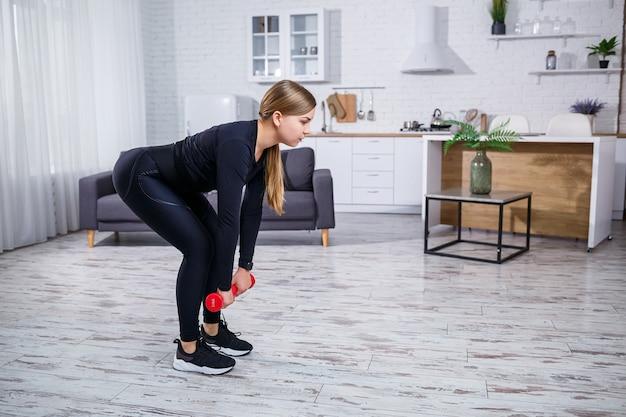 Стройная молодая женщина занимается спортом дома в топе и лосинах. фитнес в домашних условиях для красивого тела. упражнения с гантелями для женского тела. здоровый образ жизни.