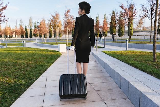 여행 가방을 들고 제복을 입은 스튜어디스의 날씬한 젊은 여성이 비행기를 타다