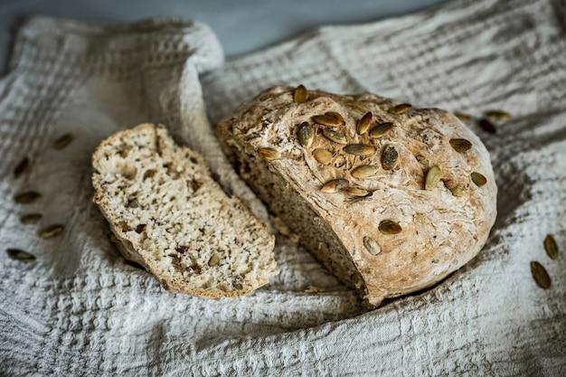 クルミとヒマワリの種が入った自家製全粒パンの新鮮なパンのスライス